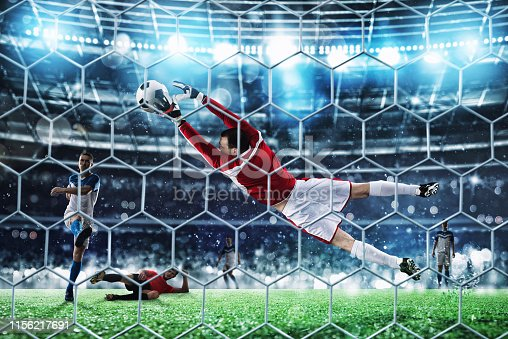 istock Goalkeeper catches the ball in the stadium during a football game 1156217691
