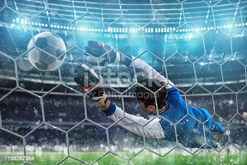 istock Goalkeeper catches the ball in the stadium during a football game 1158287354