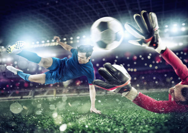 Goalkeeper catches the ball in the stadium during a football game - foto stock