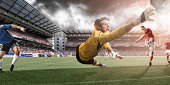 Action shot of professional goalkeeper about to make save during match in full floodlit stadium under dramatic stormy sky