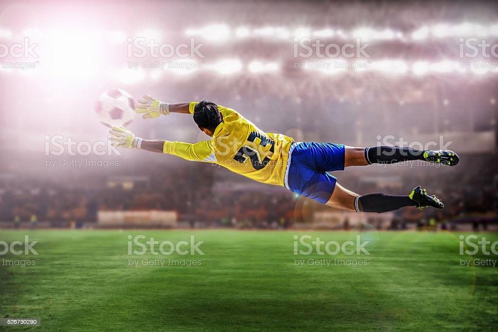 goalkeeper flying to catches the ball stock photo