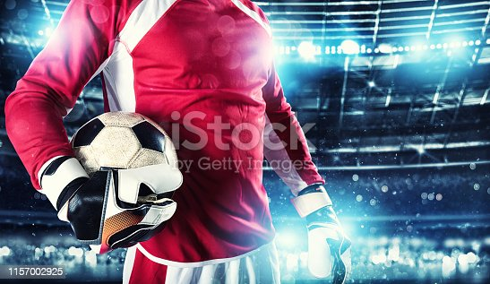 istock Goalkeeper holds the ball in the stadium during a football game 1157002925
