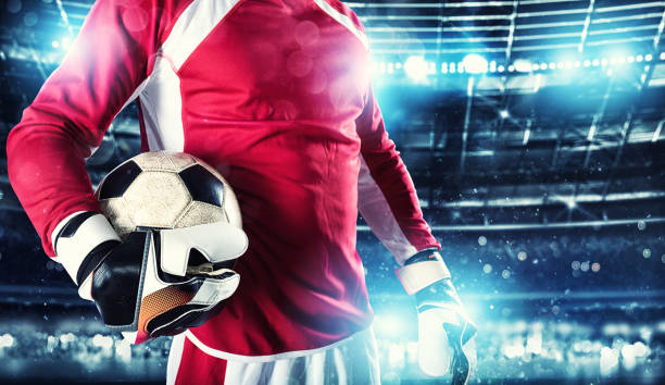 Goalkeeper holds the ball in the stadium during a football game - foto stock