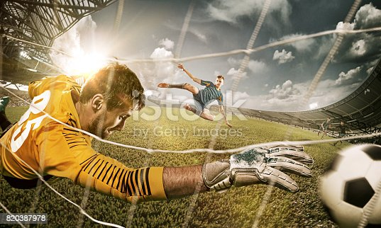 istock Goalkeeper in gates jumping to catching ball 820387978