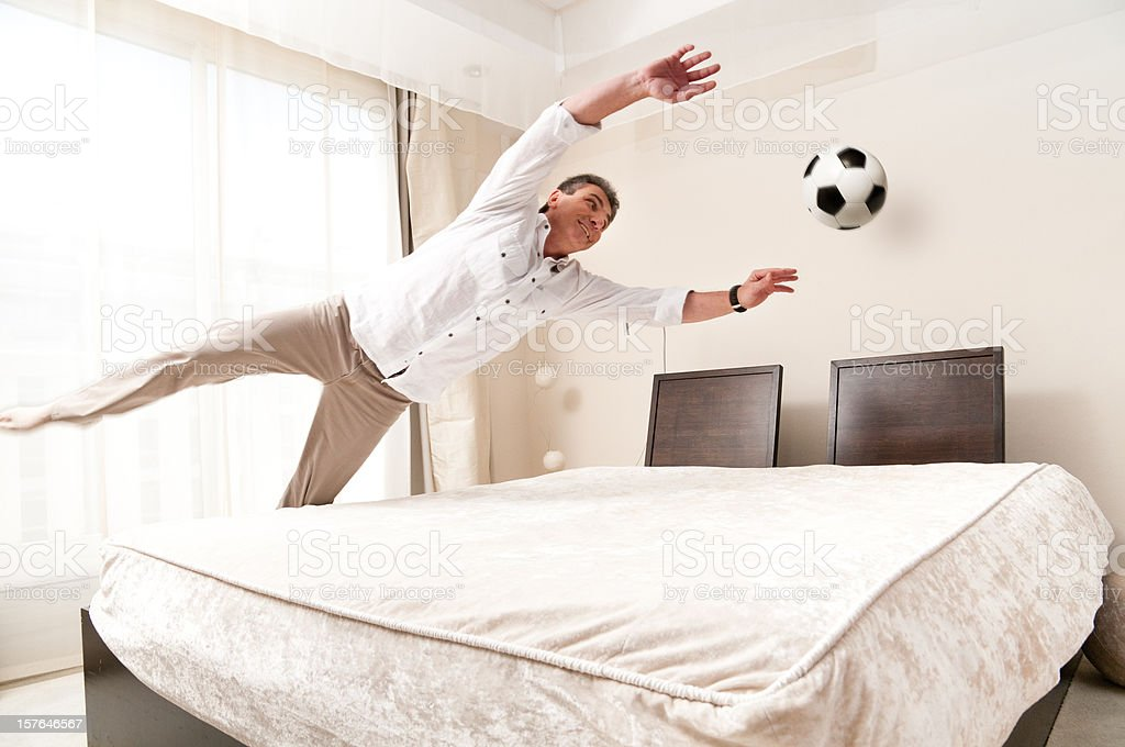 Goalkeeper training in hotel bed room royalty-free stock photo