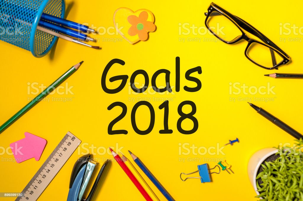Goals 2018 text on yellow board with office supplies. New Year's promises for the next year, Mock up stock photo