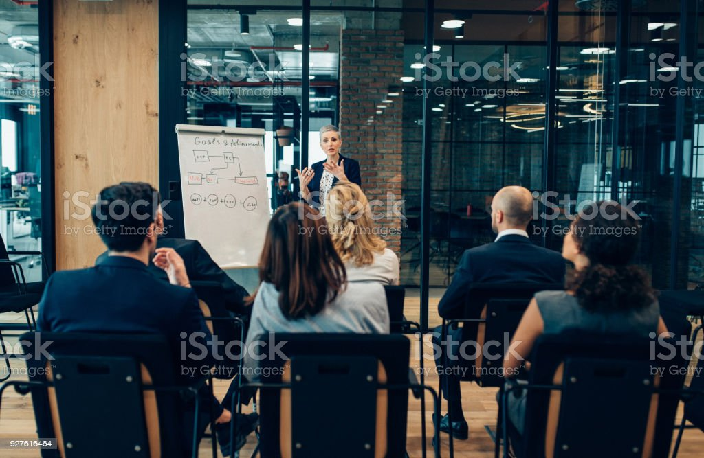 Goals and achievement Serious businesswoman giving presentation to multi-ethnic business group with flipchart Achievement Stock Photo