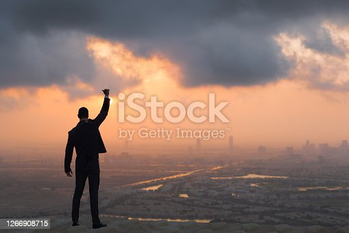 Business man with a hand and thumb up in the air. He is standing confident on top of a skyscraper with an amazing city view and colorful sky while the sun rises in the background.