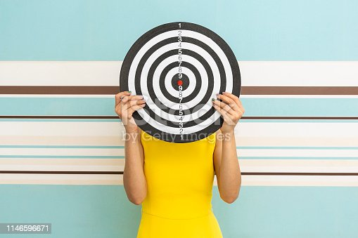 istock Goals concept with young woman holding target on blue background. 1146596671