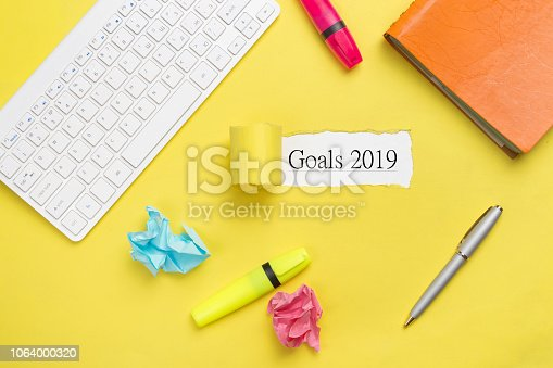 istock Goals concepts 2019. Office accessories layout - text Goals 2019 on a white background. Yellow table, keyboard, notebook and the crumpled papers 1064000320