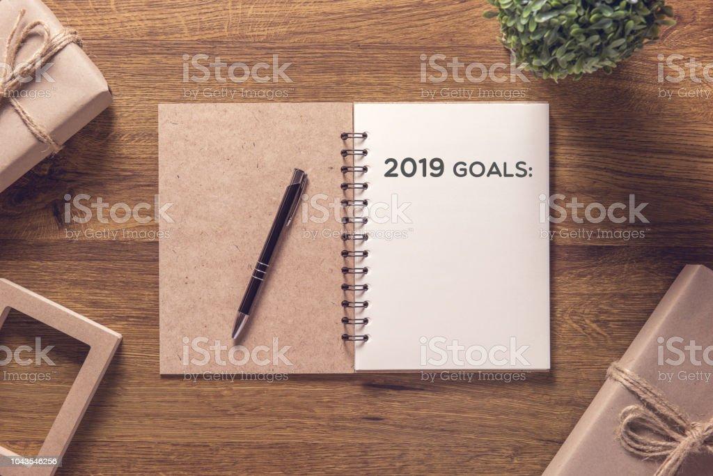 2019-Ziele-Liste im Notebook mit Geschenk Box Silvester auf dem Holztisch Hintergrund. – Foto