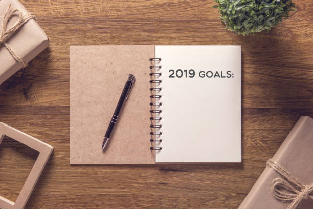 2019 goals list in notebook with gift box new year on wooden table background. stock photo