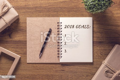 istock 2018 goals list in notebook with gift box new year on wooden table background. 859518596
