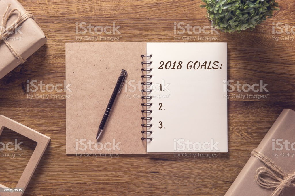 2018 goals list in notebook with gift box new year on wooden table background. stock photo