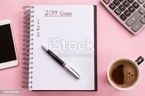 1186985932 istock photo 2019 goals list with notebook, cup of coffee over on pink background. 1084339462