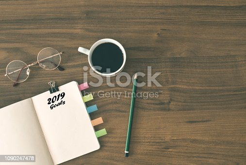 1186985932 istock photo 2019 goals list with notebook , cup of coffee over on wooden background. 1090247478