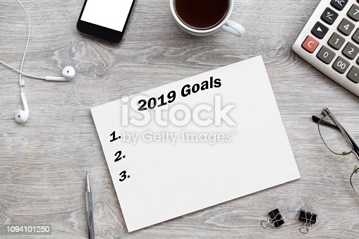 1076095678istockphoto 2019 goals list with paper, cup of coffee over on gray background. 1094101250