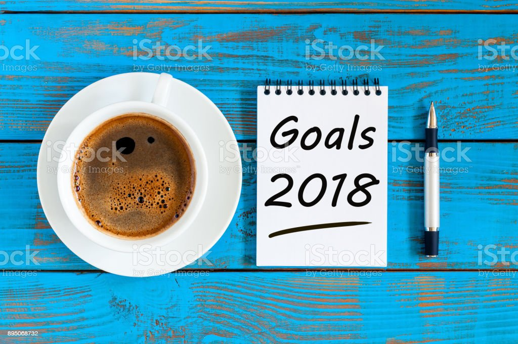 2018 goals on paper note book background and morning coffee cup on blue wood table, Targets, goal, dreams and New Year's promises for the next year stock photo