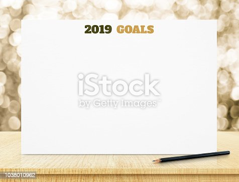 2019 goals on white paper poster on wood table with gold bokeh lights at background,mock up for adding business plan for new year