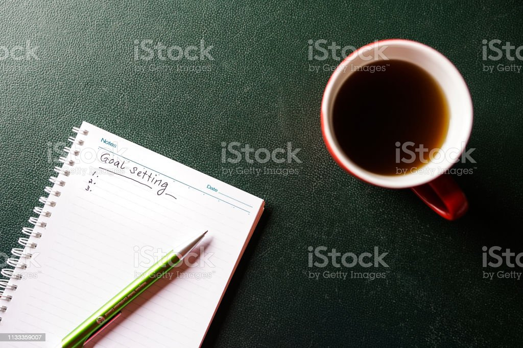 Goals setting to be written on a notebook with pen over a cup of...