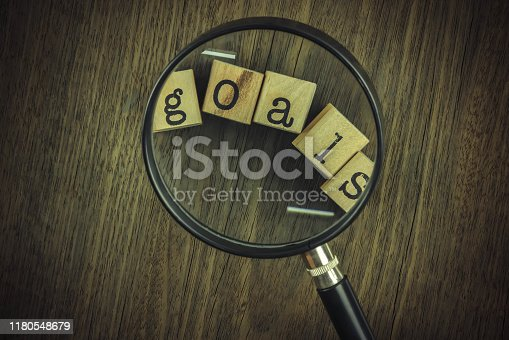 Goals setting strategy for business management. Magnifying glass focus on goals word typography over blocks and wooden table background, vintage and retro style.