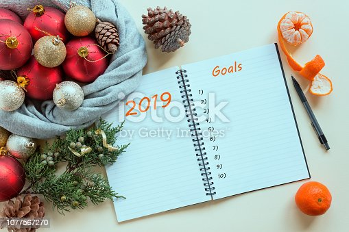 888342518istockphoto 2019 goals. To do list in notepad next to Christmas decorations, cones and tangerines. Planning concept, New year, Christmas, wishes and dreams, festive mood. 1077567270