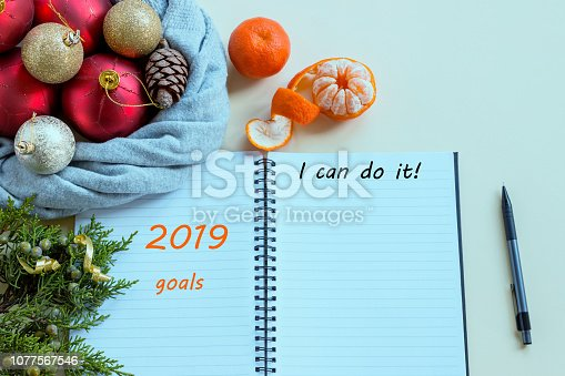 888342518istockphoto 2019 goals. To do list in notepad next to Christmas decorations, cones and tangerines. Planning concept, New year, Christmas, wishes and dreams, festive mood. 1077567546