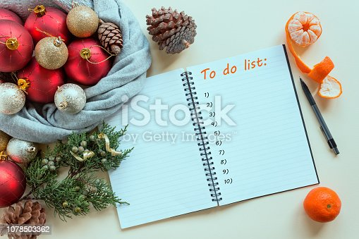 1057357020istockphoto 2019 goals. To do list in notepad next to Christmas decorations, cones and tangerines. Planning concept, New year, Christmas, wishes and dreams, festive mood. 1078503362