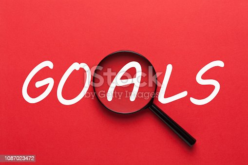 Goals written on red background and magnifying glass. Business concept