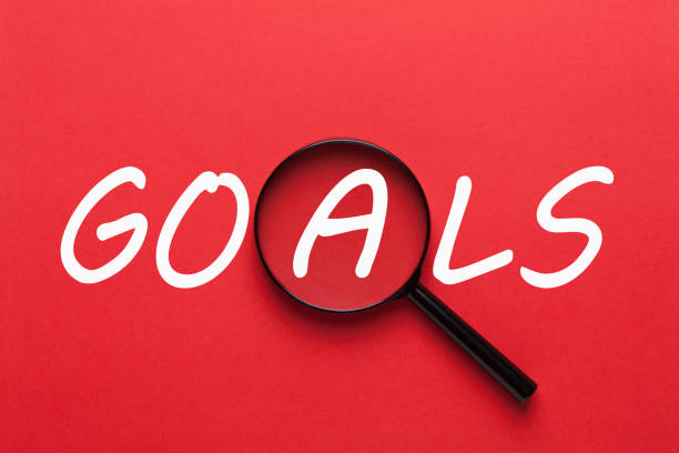 Goals with Magnifying Glass Goals written on red background and magnifying glass. Business concept arrange stock pictures, royalty-free photos & images