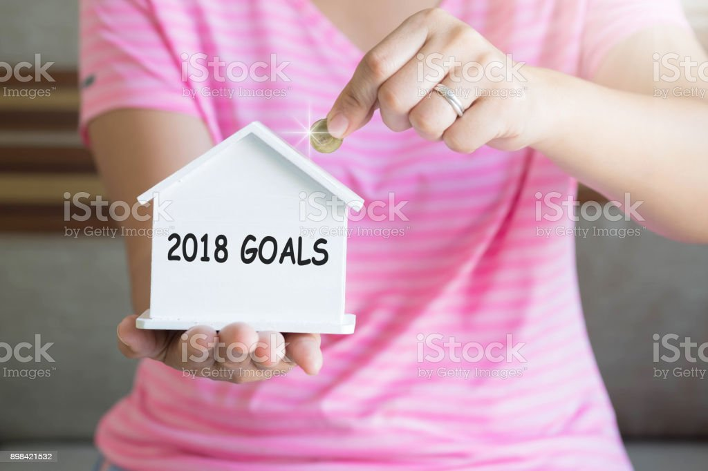 2018 goals with women hand putting money coin in piggy bank, Saving money concept, concept of financial savings to buy a house, Growth, business, money. stock photo