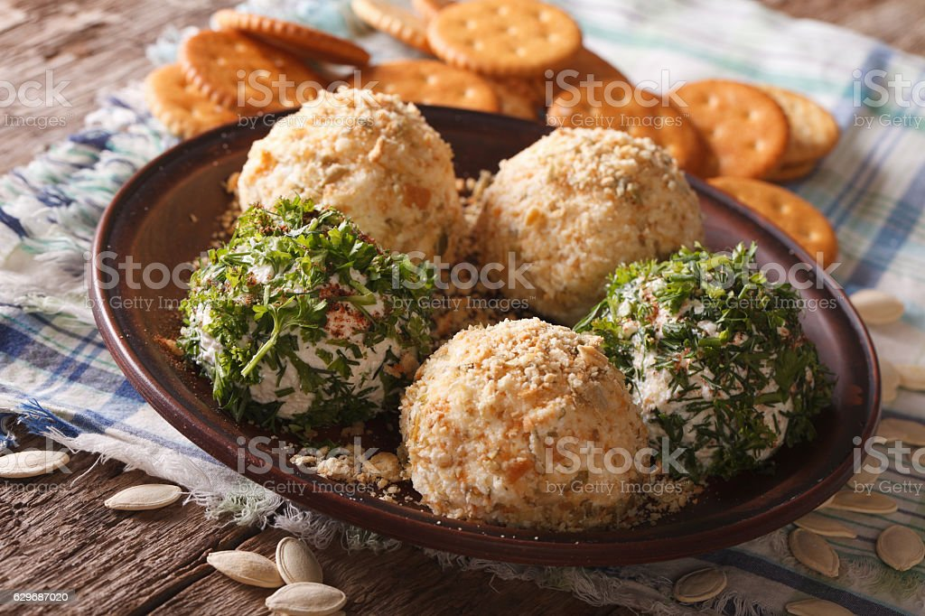 Goat Cheese balls with crackers, herbs and pumpkin seeds close-up - foto de acervo
