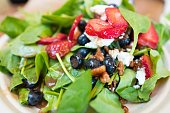 A healthy, red white and blue salad consisting of spinach, goat cheese, strawberries and blueberries, close-up on a white plate, June 23, 2017
