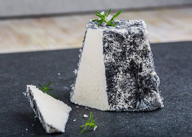 Goat cheese Valencay on a black background stock photo