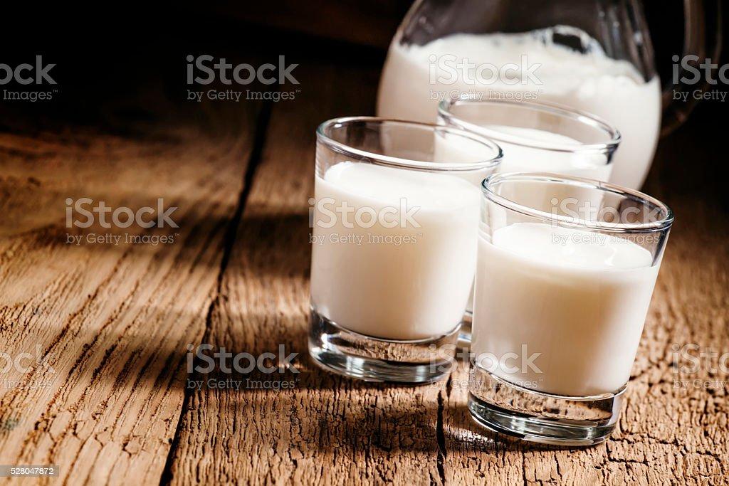 Goat milk in glasses, vintage wooden background stock photo