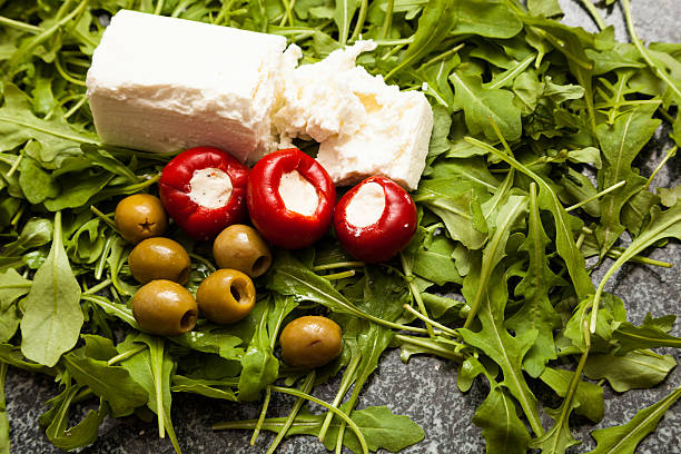 goat's cheese olives stuffed red peppers rocket on chopping board - pimento cheese stock photos and pictures