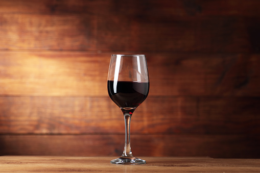 goblet with wine on the counter and wooden background