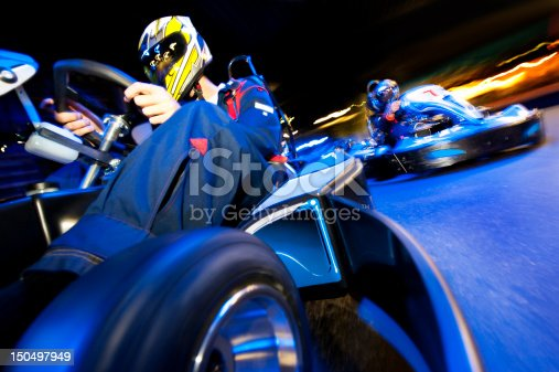 Two go-cart drivers batteling in a competitive race on an indoor circuit
