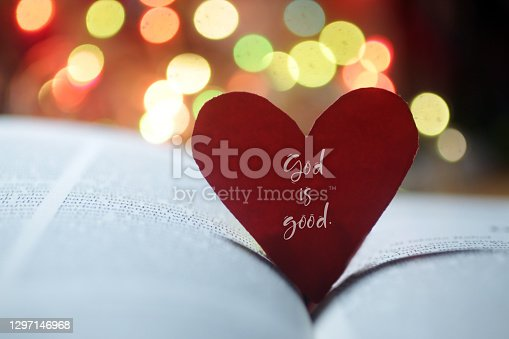Spiritual inspirational quote - God is love. With hand holding red valentines day card with heart shaped paper on an open page of bible book and colorful bokeh background.