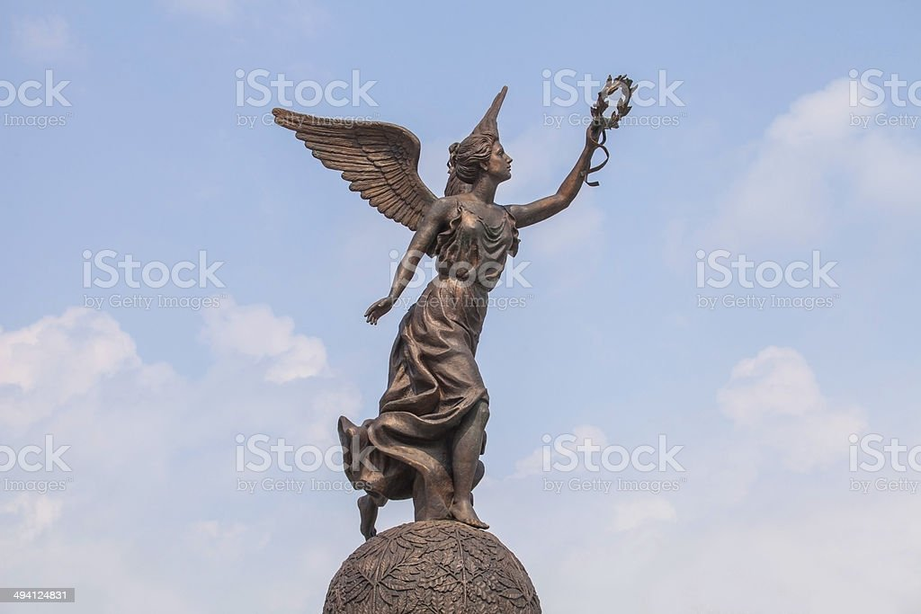 Goddess of victory Nike against the clouds and sky. stock photo