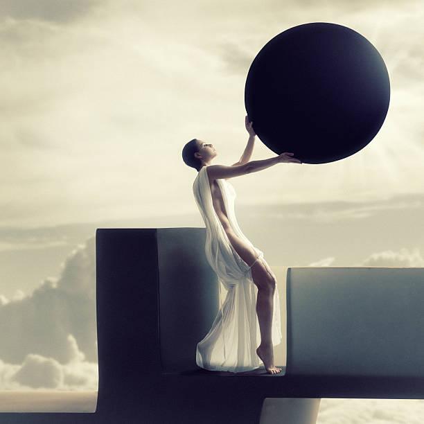 Goddess woman holding moon over sun making a solar eclipse  stock photo