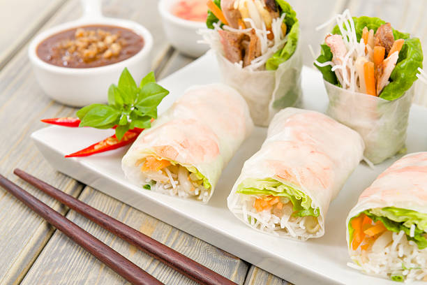 Goi cuon rolls on white plate with sauces and chopsticks Vietnamese fresh summer rolls filled with prawns, pork, herbs, rice vermicelli and vegetables served with hoisin and peanut dip and nouc mam cham. vietnamese culture stock pictures, royalty-free photos & images