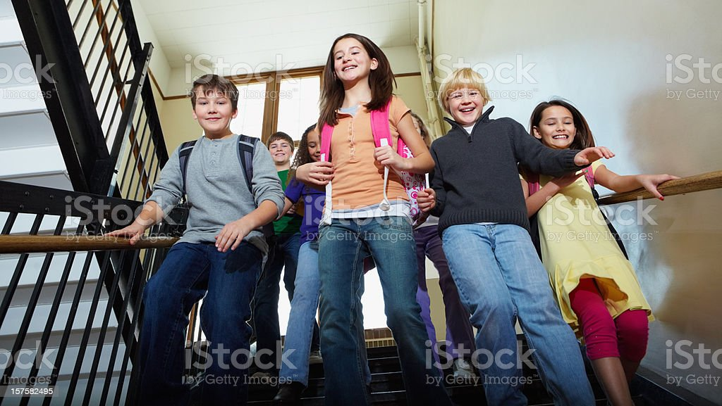 Going back home - Young multi ethnic kids at staircase stock photo