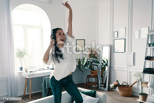 Full length of attractive young woman wearing headphones and smiling while dancing on sofa at home