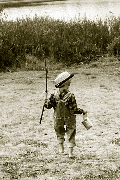 Going Fishing A photograph of a little boy going fishing.  This photograph was converted to black and white with sepia toning added to give it an old fashioned feel. bib overalls boy stock pictures, royalty-free photos & images