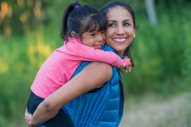 Going for a Walk with Mom A young Hispanic ethnicity family go hiking in the forest at sunset. The mother and toddler are in activewear as the toddler rider on her mother's back and laugh together. spanish and portuguese ethnicity stock pictures, royalty-free photos & images