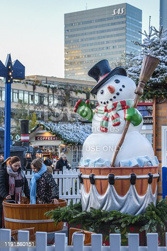 """Copenhagen, Denmark, November 30, 2019: Visiting Tivoli is one of the """"must dos"""" when in Copenhagen. About 5 million people visit Tivoli each divided into four seasons: Easter, Summer, Halloween in Tivoli and Christmas in Tivoli. The gardens are well visited by tourists as well as Danes. Many people living in Copenhagen have a yearly card to visit the park whenever they want.   Christmas season goes from the middle of November, until the first week in January.  During Christmas in Tivoli there is a market with small and cute cottage like stalls selling food and drink, clothing, toys and items for the home."""