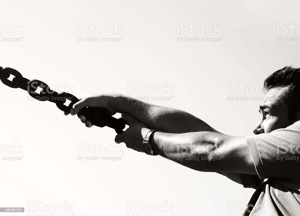 Going further - Man pulling a chain royalty-free stock photo