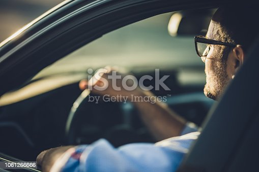 Young businessman driving a car while going on a trip.