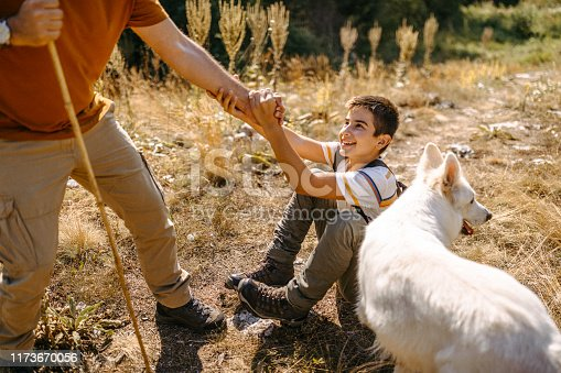 Father and son starting hiking adventure with their dog in mountain, man helping son to get up